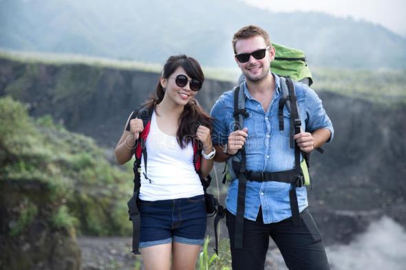 jovem-mulher-e-o-homem-vão-trekking-junto-fundo-da-natureza-64902171